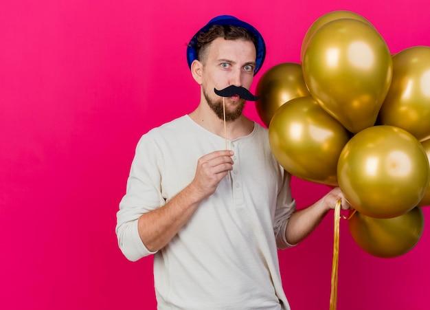 Zabawny młody przystojny słowiański imprezowicz w kapeluszu imprezowym, trzymając balony i fałszywe wąsy na patyku nad ustami, patrząc z przodu, robi gest pocałunku na różowej ścianie z miejscem na kopię