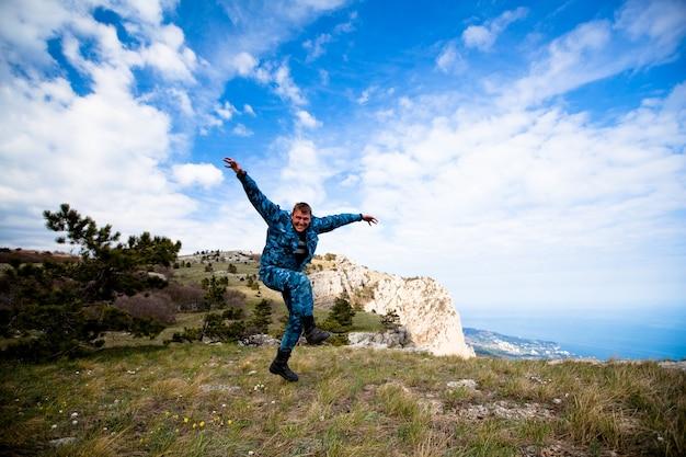 Zabawny młody wesoły kaukaski mężczyzna skoki na wzgórzach z zieloną trawą przeciw błękitne niebo i białe chmury. pojęcie długo oczekiwanych podróży i turystyki