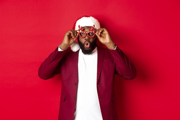 Zabawny murzyn świętujący nowy rok, noszący okulary na imprezę i santa hat, bawiący się na czerwonym tle