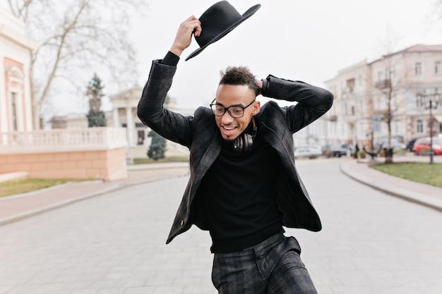 Zabawny murzyn wygłupia się podczas plenerowej sesji zdjęciowej w parku. chłodny afrykanin w eleganckim stroju, cieszący się spacerem ulicą w zimny dzień.