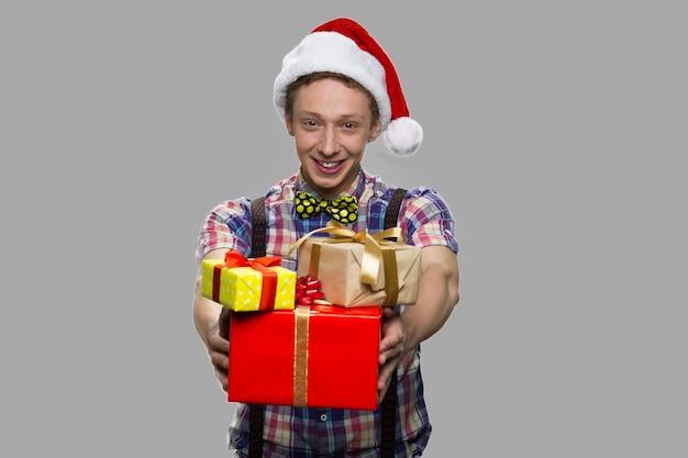 Zabawny nastolatek facet wręczający pudełka na prezenty świąteczne. boże narodzenie nastolatek chłopiec z stos pudełek prezentów szczęśliwy na szarym tle. obchody ferii zimowych.