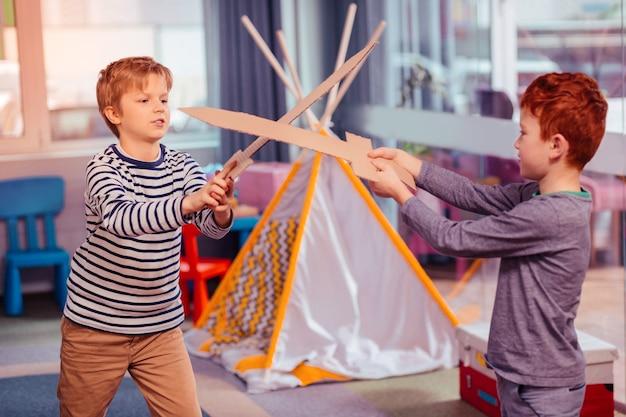 Zabawny nastrój. dwoje odważnych dzieciaków trzymających miecz i myślących o zwycięstwie