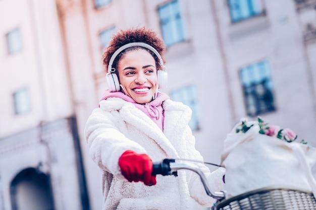 Zabawny nastrój. ładna brunetka kobieta wyrażająca pozytywne nastawienie podczas jazdy na rowerze