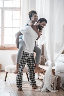Zabawny nastrój. uśmiechnięty młody brodaty ciemnoskóry mężczyzna trzyma radosną żonę na ramionach w domu w jasnym pokoju