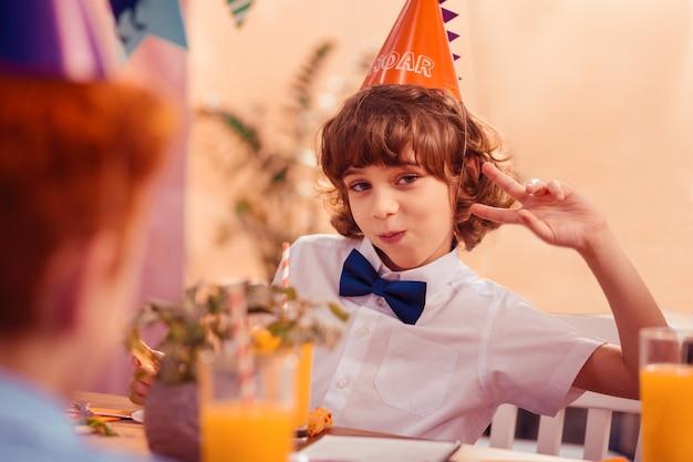 Zabawny nastrój. wesoły chłopak, utrzymując uśmiech na twarzy i nosząc urodzinowy kapelusz