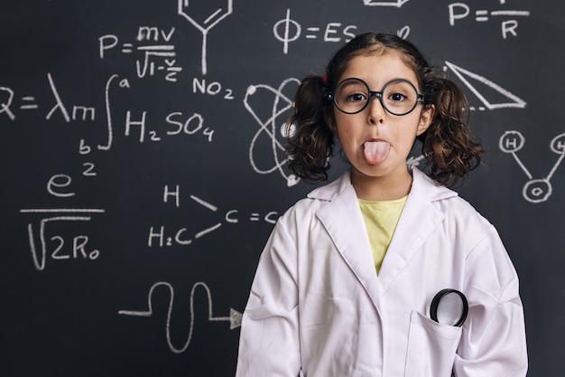 Zabawny naukowiec dziewczynka wystaje język