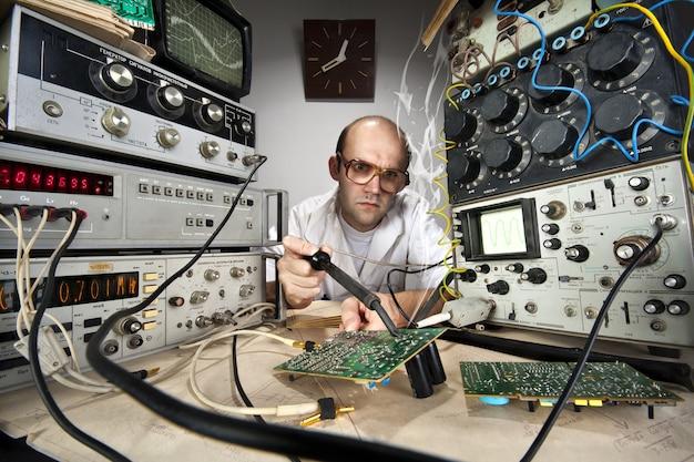 Zabawny naukowiec nerd lutowania w laboratorium vintage