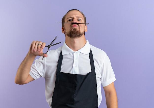 Zabawny niedojrzały młody przystojny fryzjer w mundurze trzymającym nożyczki i trzymający grzebień, aby naśladować jego fałszywe wąsy odizolowane na fioletowo z miejsca na kopię