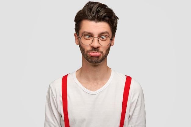 Zabawny nieogolony mężczyzna krzyżuje oczy i zaciska usta, robi grymas, ma komiczny wyraz, wygłupia się w domu na białej ścianie. stylowy, brodaty mężczyzna rasy kaukaskiej nie ma nic do roboty.
