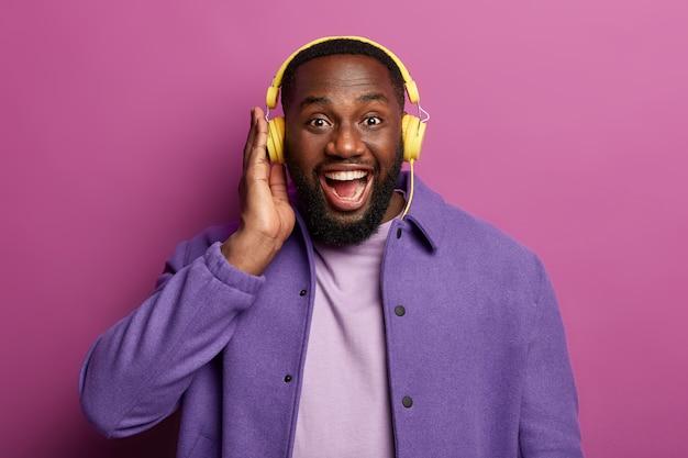 Zabawny nieogolony mężczyzna o zdrowej ciemnej skórze cieszy się głośnym dźwiękiem w słuchawkach stereo, śmieje się ze szczęścia, spędza wolny czas przy ulubionej muzyce