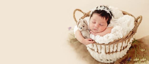 Zabawny noworodek śpiący w koszyku na brzuchu
