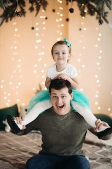 Zabawny ojciec trzymający córkę na ramionach