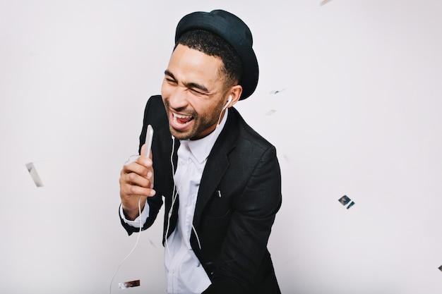 Zabawny podekscytowany młody człowiek w garniturze zabawy, śmiejąc się. wypoczynek, uśmiech, śpiew, słuchanie muzyki, wyrażanie pozytywności, prawdziwe emocje.