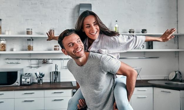 Zabawny poranek młodej pary w kuchni. uśmiechnięty brodaty mężczyzna spędza czas ze swoją ładną dziewczyną.