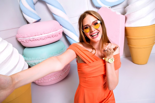 Zabawny portret kobiety blondynka robi selfie, uśmiechając się i krzycząc, okulary przeciwsłoneczne w kształcie serca, modną sukienkę blond włosy. kolory pastelowe, widok słodyczy wielkiej buzi, lody, makaroniki.