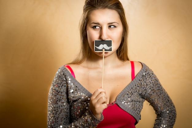 Zabawny portret młodej kobiety trzymającej wąsy na ozdobnej tablicy