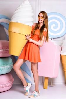 Zabawny portret mody ładnej blondynki kobiety trzymającej gigantyczne lody, pozujący w pobliżu dużej fałszywej słodyczy, pastelowych kolorów, ładnej sukienki, cukierni.