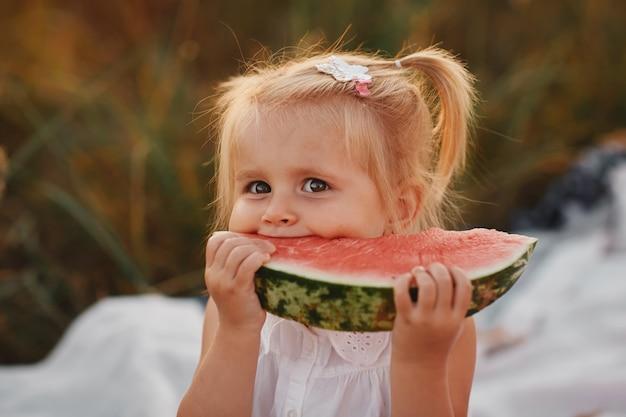 Zabawny portret niesamowicie pięknej rudowłosej dziewczynki jedzenie arbuza, przekąska zdrowych owoców, urocze dziecko malucha z kręconymi włosami grając w słonecznym ogrodzie w gorący letni dzień. portret