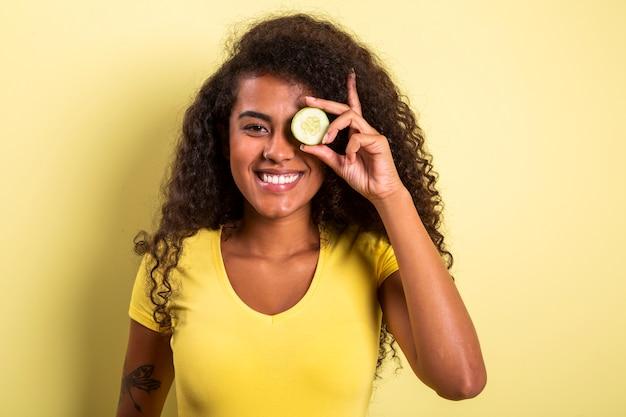 Zabawny portret pięknej czarnej modelki afrykańskiej trzymającej plaster ogórka do oka, odmładzający reżim pielęgnacji skóry zabieg koncepcja piękna twarzy.
