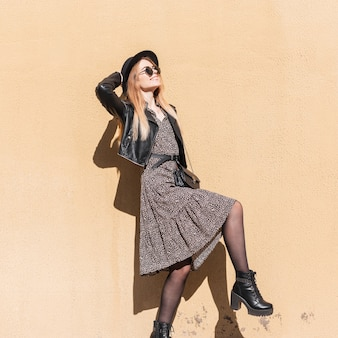 Zabawny portret pięknej szczęśliwej kobiety noszącej okulary przeciwsłoneczne w modnym wyglądzie z sukienką, skórzaną kurtką i butami pozowanie w pobliżu beżowej ściany. moda i uroda