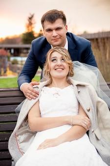 Zabawny portret przystojnego pana młodego przytulający piękną pannę młodą siedzącą na ławce