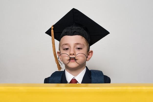 Zabawny portret ucznia w akademickim kapeluszu i dużych okularach