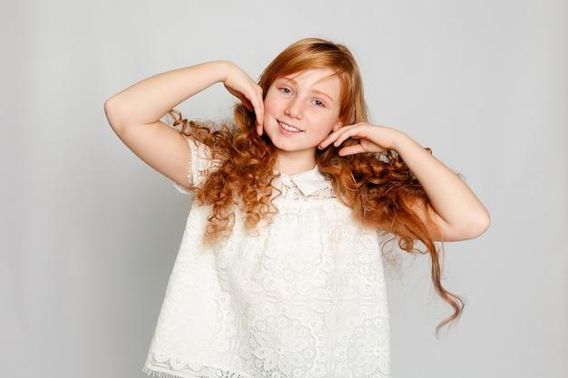 Zabawny portret urocza rudowłosa dziewczyna na szarym tle. uroda, moda dziecięca, kosmetyki, zdrowe włosy. fryzjer, makijaż, szampon.