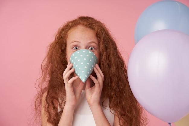 Zabawny portret uroczej rudowłosej kręconej kobiety, która pozytywnie patrzy na aparat z szeroko otwartymi oczami, oszukuje na różowym tle z czapką urodzinową i balonami powietrznymi