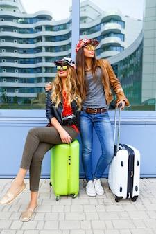 Zabawny portret życia najlepszych przyjaciółek, które bawią się przed podróżą, pozują z bagażem w pobliżu lotniska, noszą jasne, sportowe ubrania i okulary przeciwsłoneczne, gotowe na nowe emocje