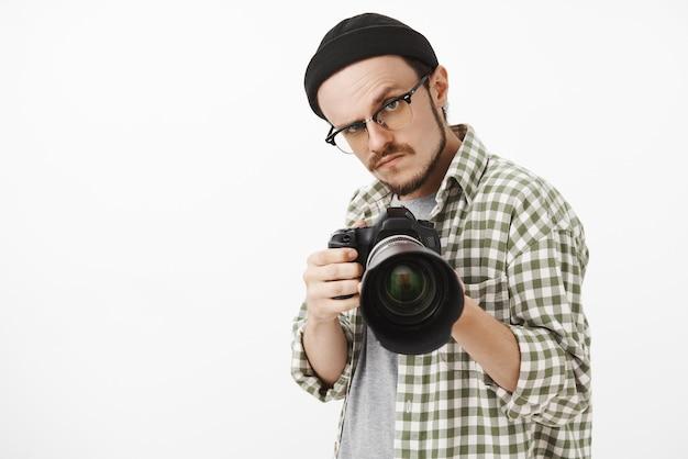 Zabawny, poważnie wyglądający męski fotograf w czarnych okularach typu beanie i koszuli w kratkę, skierowany profesjonalnym aparatem do przodu i poważnym spojrzeniem, by zrobić zdjęcie podczas pracy