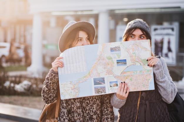 Zabawny pozytywny obraz modnych kobiet na słonecznej ulicy bawiących się w mieście, chowających się za mapą miasta. wspólne podróże, najlepsi przyjaciele, zgubienie się w wielkim mieście, prawdziwe emocje.