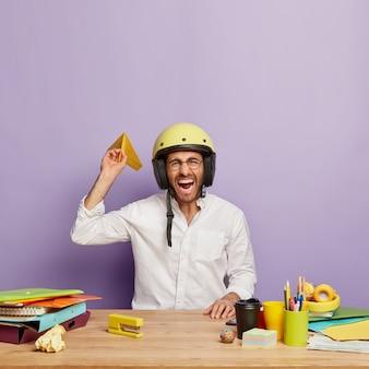 Zabawny pracownik siedzi przy biurku