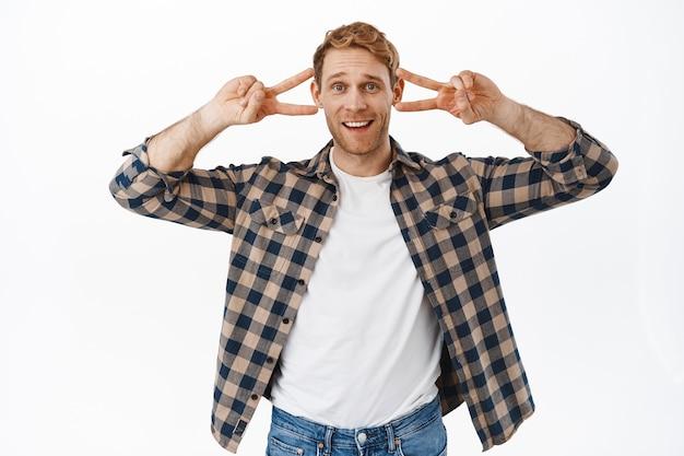 Zabawny przystojny dorosły mężczyzna tańczący, pokazujący znak pokoju i uśmiechający się, bądź pozytywny, rozweselaj się, wygłupiaj się i pokazując zabawne twarze, stojąc nad białą ścianą