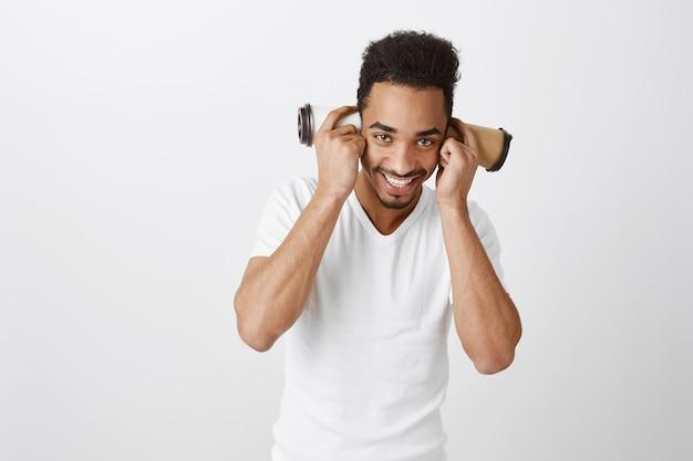 Zabawny przystojny facet afroamerykanin bawiący się papierowymi kubkami i uśmiechnięty szeroko