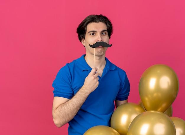 Zabawny przystojny kaukaski mężczyzna w niebieskiej imprezowej czapce trzyma balony z helem i sztuczne wąsy na patyku