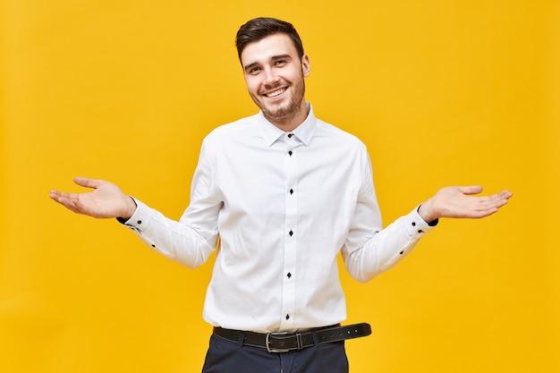 Zabawny, przystojny, młody kaukaski mężczyzna w białej koszuli robi bezradny gest, wzrusza ramionami, zagubiony, uśmiechnięty, ma zapominający zdezorientowany wyraz twarzy, mówiący nie wiem lub kto wie