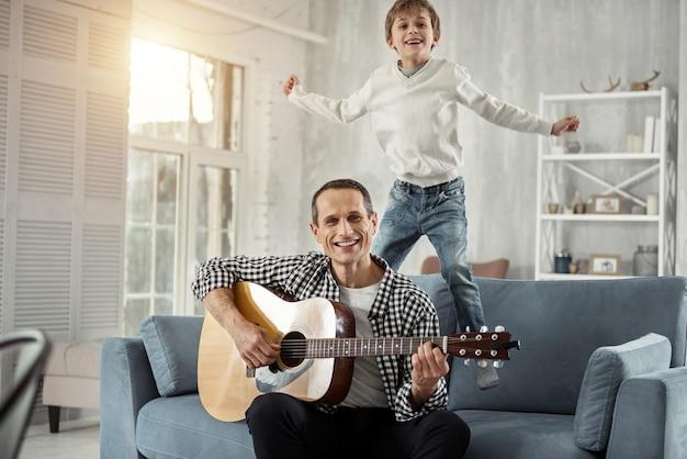 Zabawny. przystojny radosny ciemnowłosy mężczyzna uśmiecha się i gra na gitarze, a jego syn skacze za nim na kanapie i uśmiecha się