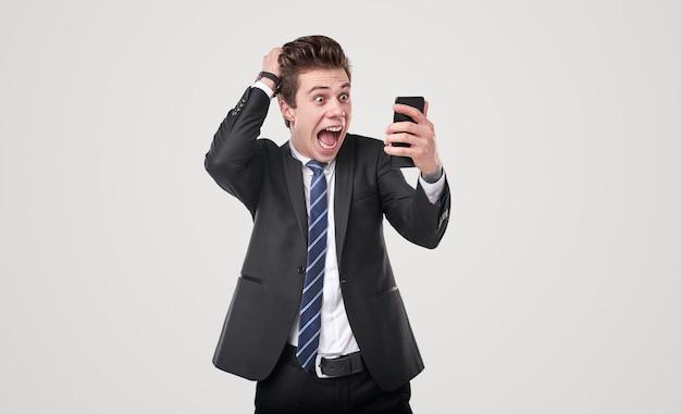 Zabawny przytłoczony młody męski kierownik wykonawczy w formalnym garniturze czyta szokujące wiadomości na telefonie komórkowym i krzyczy ze zdumienia na białym tle