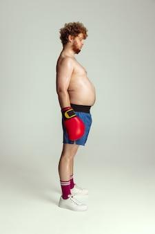 Zabawny rudowłosy mężczyzna w niebieskich bokserskich spodenkach i rękawiczkach odizolowanych na szaro