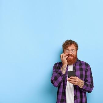 Zabawny rudy mężczyzna z nerwowym wyrazem twarzy, gryzie paznokcie
