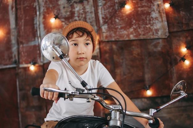 Zabawny, słodki chłopiec w klatce piersiowej i biała koszulka na motocyklu przedstawia się jako dorosły i fajny