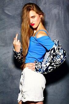Zabawny styl życia szalony seksowny stylowy seksowny uśmiechnięty piękny blond młoda kobieta model w lecie hipster jasny materiał w pobliżu szarej ścianie