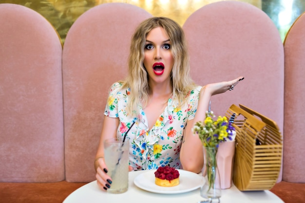 Zabawny stylowy portret kobiety blondynka pozowanie w kawiarni słodkie jedzenie deser, szalone zaskoczone emocje, koncepcja diety, styl pin up.