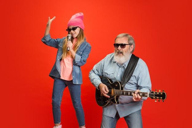 Zabawny, stylowy. starszy mężczyzna spędza szczęśliwy czas z wnuczką w neonie.