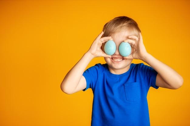 Zabawny szczęśliwy chłopiec na żółtym tle, motyw wielkanocny