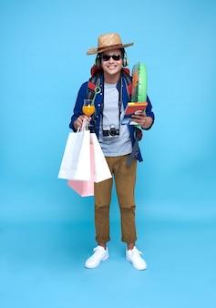 Zabawny szczęśliwy człowiek azji z plecakiem na niebieskim tle.