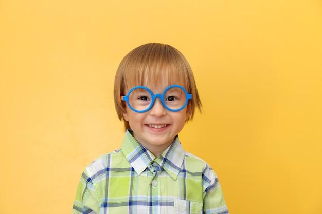 Zabawny szczęśliwy mały chłopiec w okularach i koszuli z uśmiechem