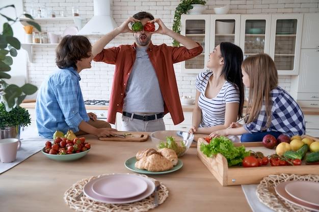 Zabawny tata bawi się słodką papryką podczas wspólnego gotowania z rodziną w nowoczesnej kuchni w