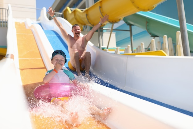 Zabawny tata i córka jeżdżą na zjeżdżalniach wodnych. rodzina spędza czas w aquaparku.