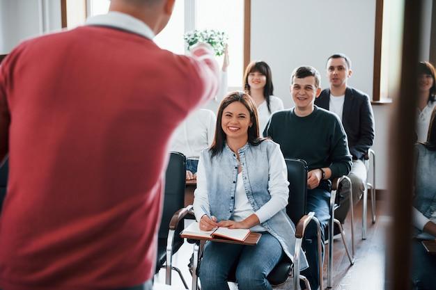 Zabawny trener. grupa ludzi na konferencji biznesowej w nowoczesnej klasie w ciągu dnia